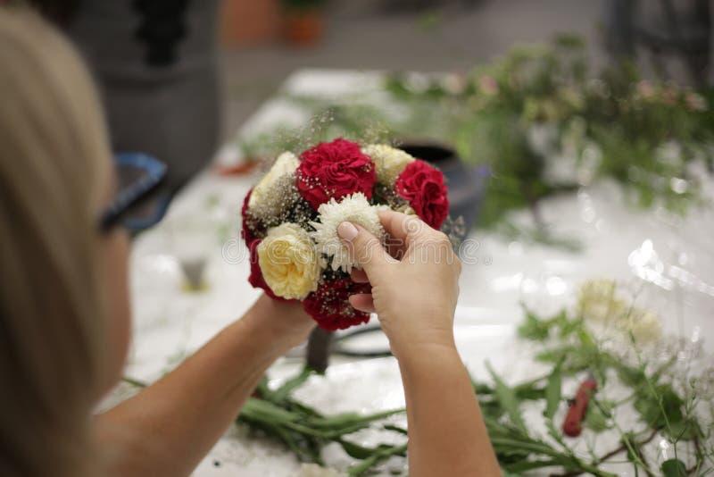 Dziewczyna dekoruje bukiet od różnych kwiatów zdjęcia stock