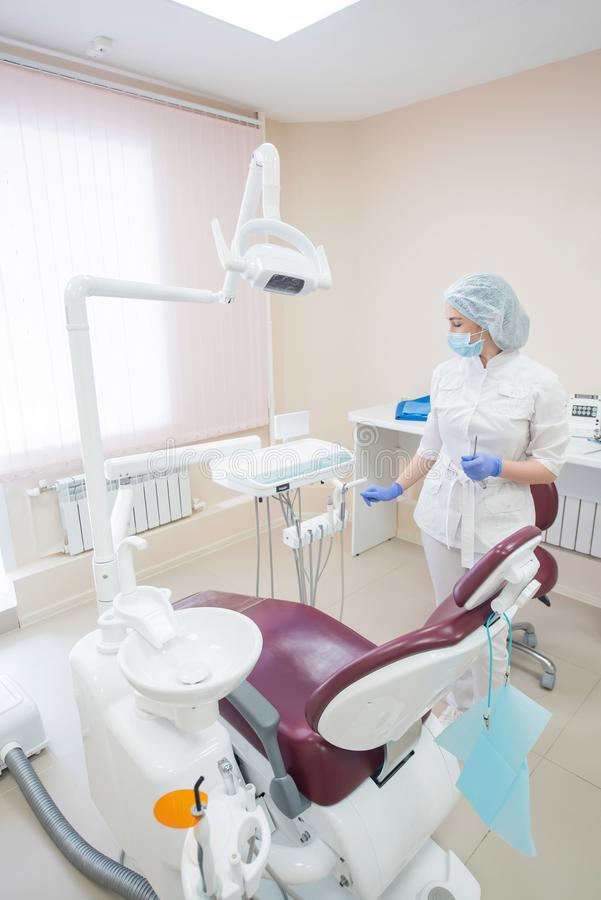 Dziewczyna dentysta w biel ubraniach, masce i nakrętka stojakach obok nowożytnego stomatologicznego krzesła w, wielkim, prostym,  obrazy royalty free
