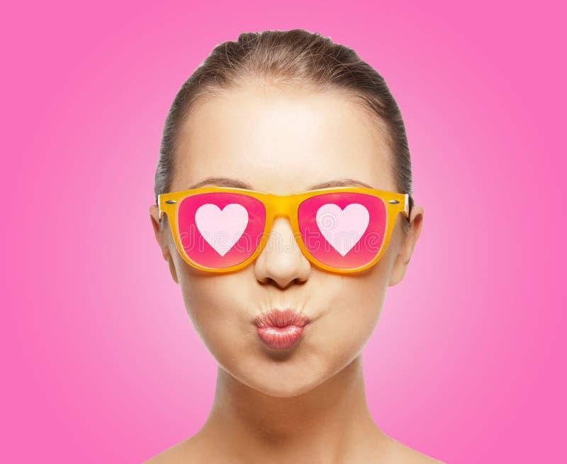 Dziewczyna dmucha buziaka w różowych okularach przeciwsłonecznych zdjęcia stock
