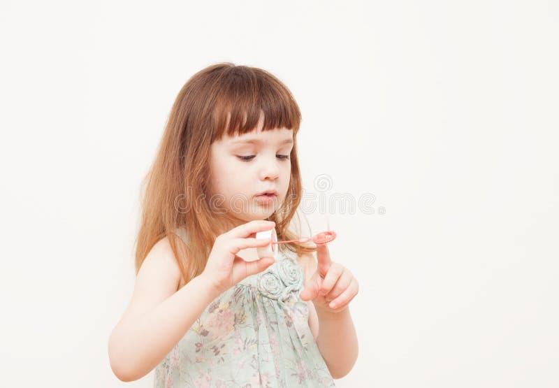 Dziewczyna dmucha mydlanych bąble na monophonic tle zdjęcie stock