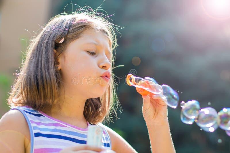 Dziewczyna dmucha mydlanych bąble w parku w słonecznym dniu obrazy royalty free