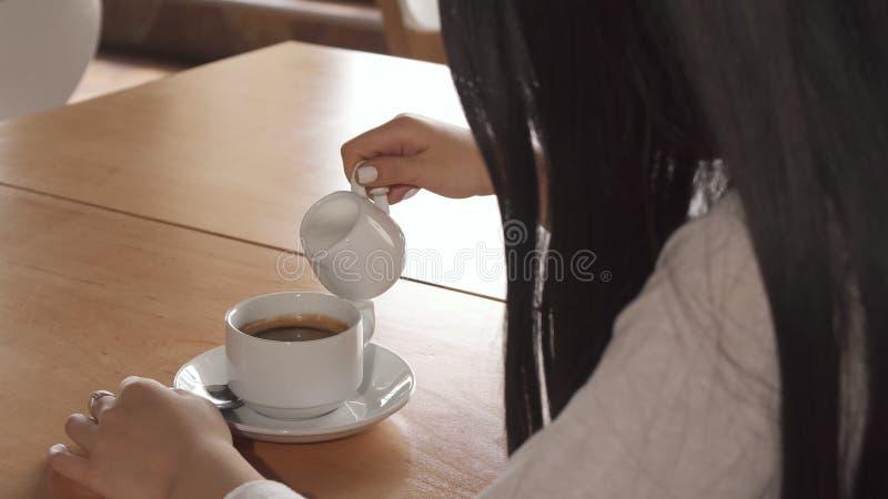 Dziewczyna dodaje śmietankę w jej kawę przy kawiarnią fotografia stock
