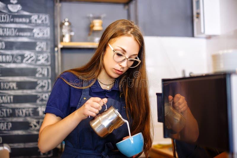 Dziewczyna dodaje mleko filiżanka z kawą w kawiarni Młodej kobiety barista pracuje w sklep z kawą zdjęcia royalty free