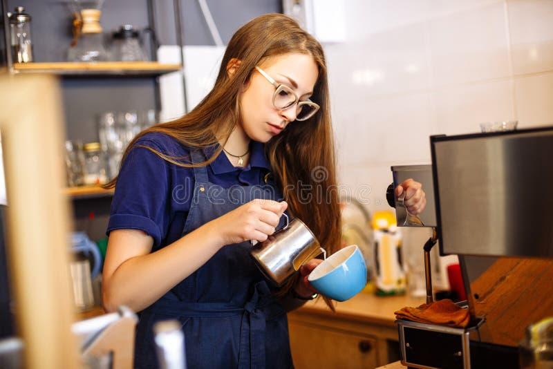 Dziewczyna dodaje mleko filiżanka z kawą w kawiarni Młodej kobiety barista pracuje w sklep z kawą zdjęcie stock