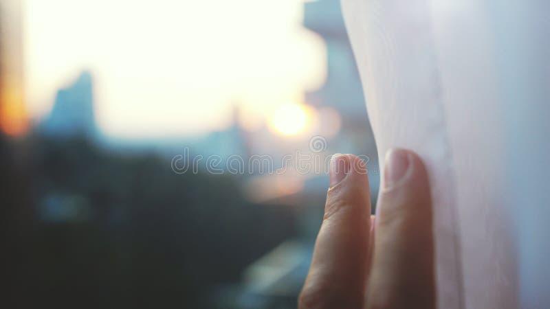 Dziewczyna dotyka światło słoneczne ręką w jej pokoju w domu Żeńska ręka otwiera zasłony obraz royalty free