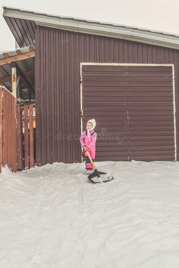 Dziewczyna, dziecko duża łopata usuwa śnieg od ścieżki w podwórko przy garażem obraz royalty free