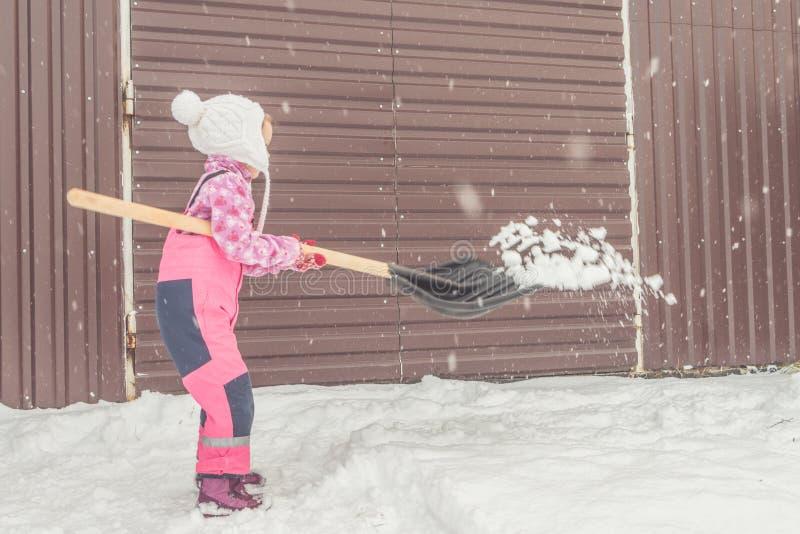 Dziewczyna, dziecko duża łopata usuwa śnieg od ścieżki w podwórko przy garażem zdjęcie stock