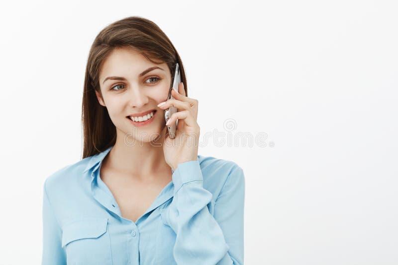 Dziewczyna dzwoni matki od pracy Portret pozytywny szczęśliwy śliczny żeński coworker w błękitnej bluzce, trzyma smartphone nowy zdjęcia stock