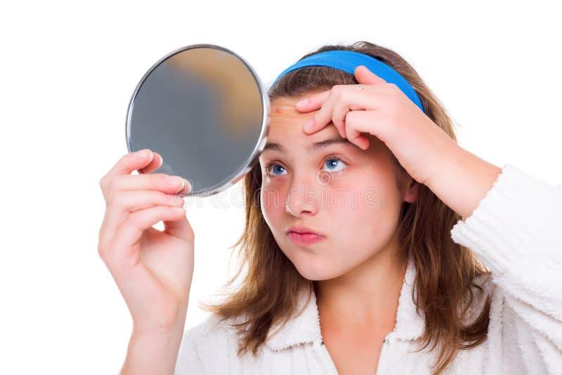 Dziewczyna egzamininuje jej krosty w lustrze fotografia stock