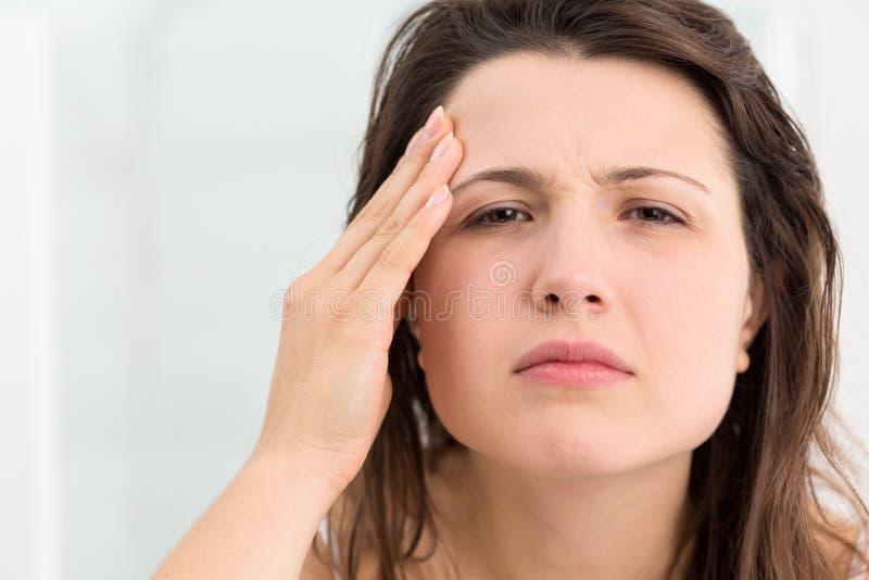 Dziewczyna egzamininuje jej twarzy skórę obrazy stock