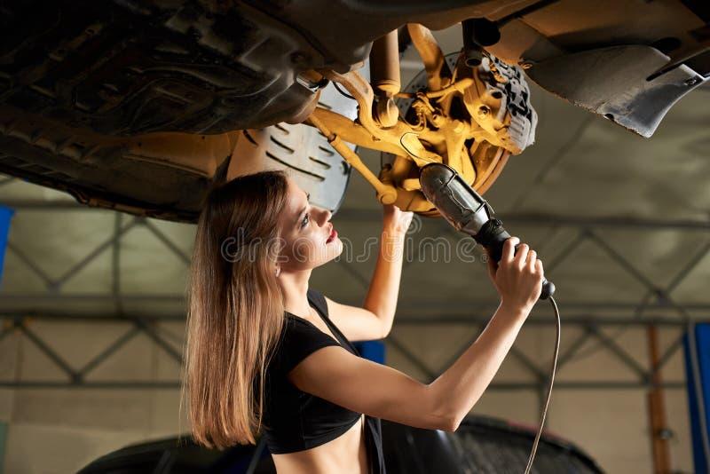 Dziewczyna egzamininuje podnoszącego samochód z lampą obrazy royalty free