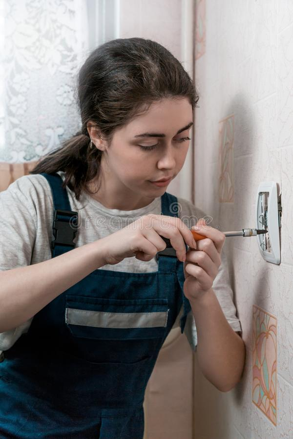 Dziewczyna elektryk naprawia ujście na ścianie z śrubokrętem obrazy royalty free
