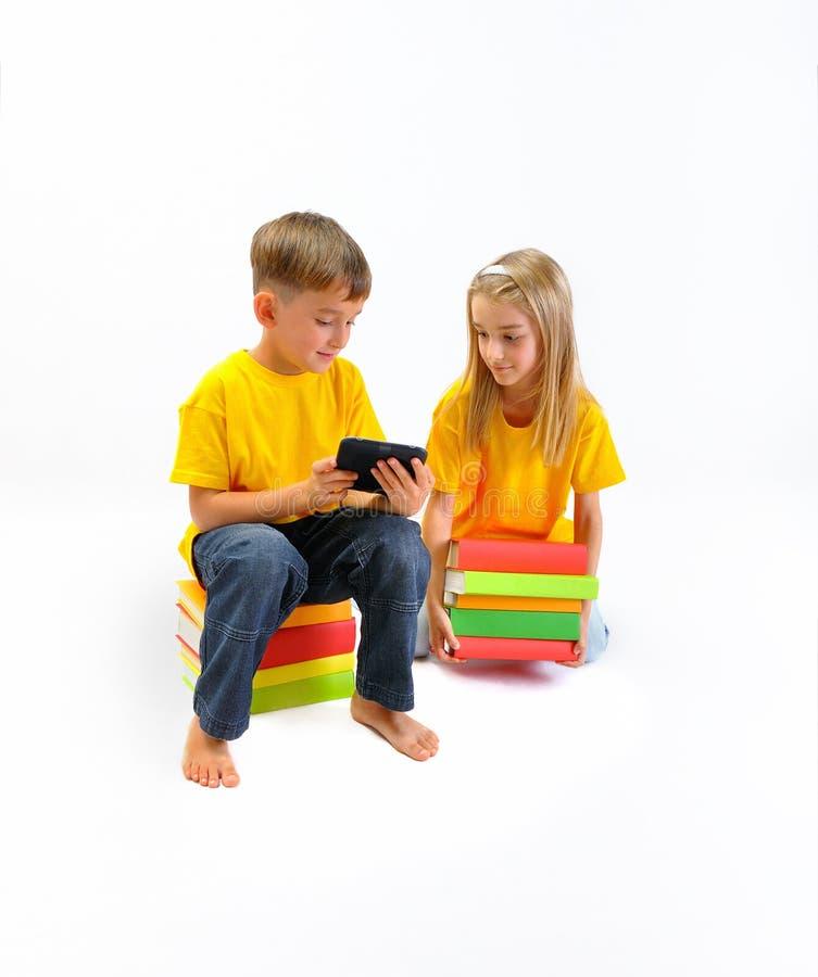 Dziewczyna few książki, chłopiec pokazuje ona ebook obrazy stock
