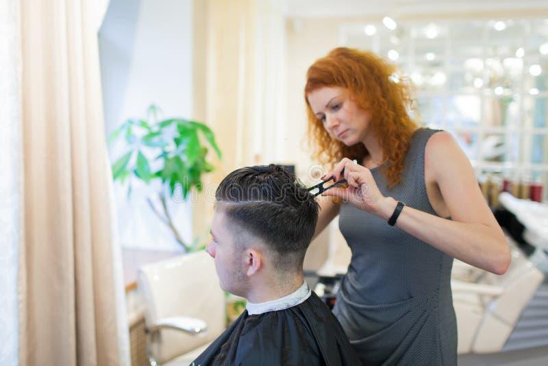 Dziewczyna fryzjer z kędzierzawym czerwonym włosy ciie potomstwa, przystojny facet w piękno salonie zdjęcia stock