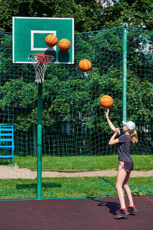 Dziewczyna gracz koszykówki rzuca piłkę w koszu obrazy royalty free