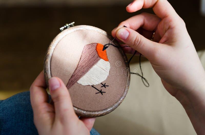 Dziewczyna haftuje ptaka z ściegiem DIY pojęcie, hobby, twórczość, odzież i wewnętrzna dekoracja, fotografia stock