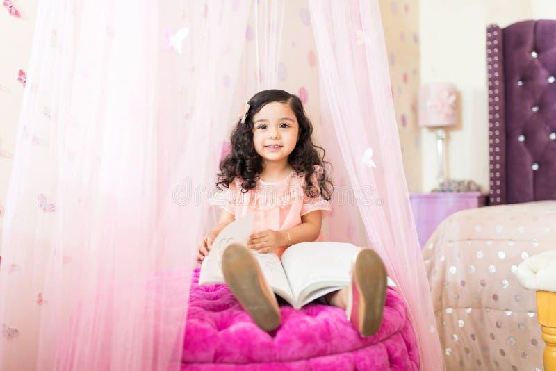Dziewczyna Iść Przez książki Na Seat W Princess sypialnia zdjęcie stock