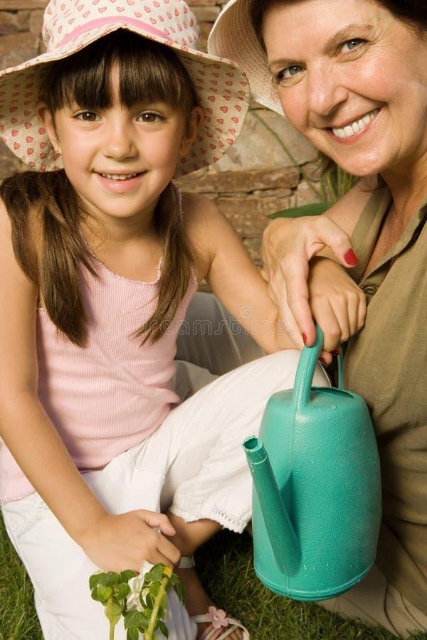 Dziewczyna i babcia z podlewanie puszką fotografia stock