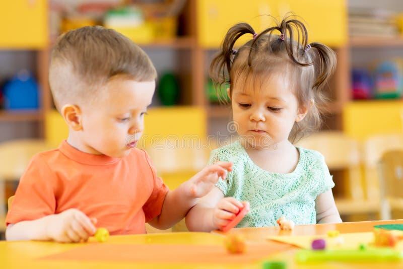 Dziewczyna i chłopak bawiący się przy stole z zabawkami edukacyjnymi Dzieci w domu lub opiece dziennej obraz stock