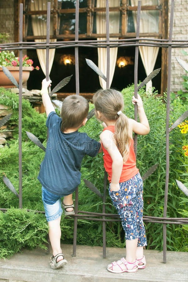 Dziewczyna i chłopiec oglądamy kawiarni z ciekawością za od ogrodzenia fotografia stock