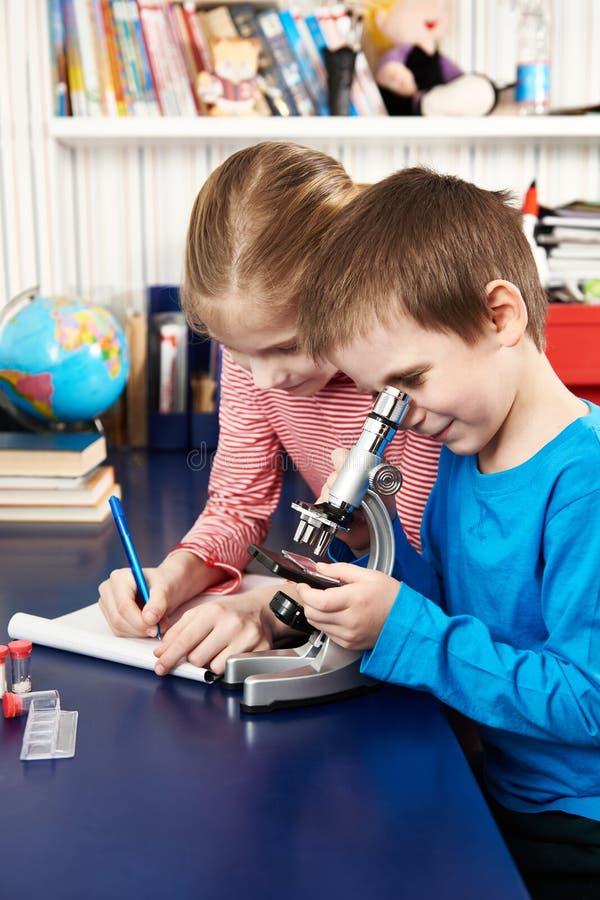 Dziewczyna i chłopiec używamy mikroskop i piszemy rezultatach zdjęcie stock