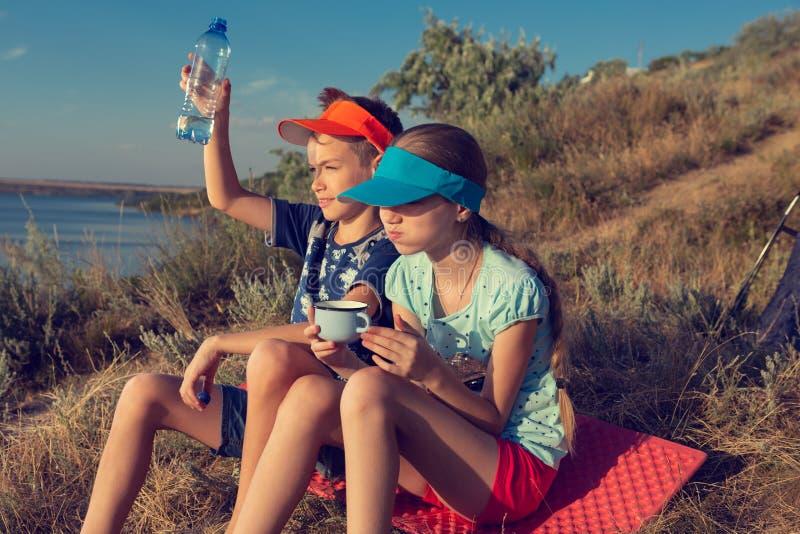 Dziewczyna i chłopiec w podwyżce lub na pinkinie, siedzimy na macie i napój woda chłopiec podnosił butelkę woda nad jego głową po zdjęcie royalty free