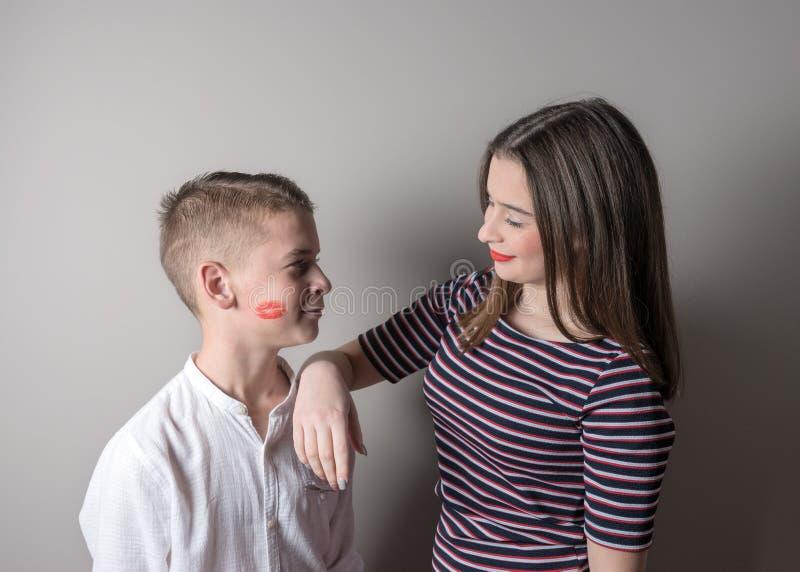 Dziewczyna i chłopiec z pomadką całujemy na jego twarzy na jaskrawym tle fotografia royalty free