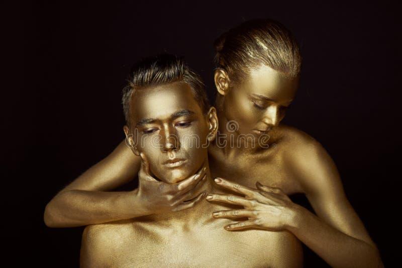 Dziewczyna i chłopiec zakrywający w złocistej farbie, Z mój oczami zamykającymi Zginał puszek on Patrzeje w różnych kierunkach _ obraz royalty free