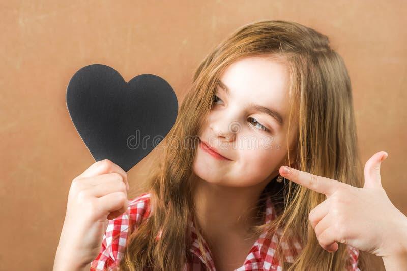 Dziewczyna i czerni łupkowy serce Dziewczyna buduje fizjognomię, grymasy i serce dla inskrypcji, Walentynka dnia pojęcie, zakończ zdjęcie stock