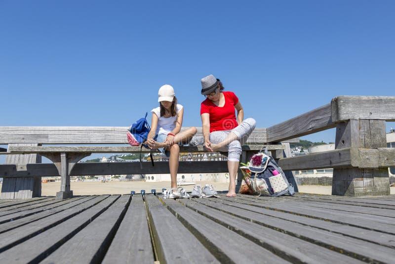 Dziewczyna i jej matka czyścimy ich cieki piasek przy Angielskim kanałem w Trouville zdjęcia stock