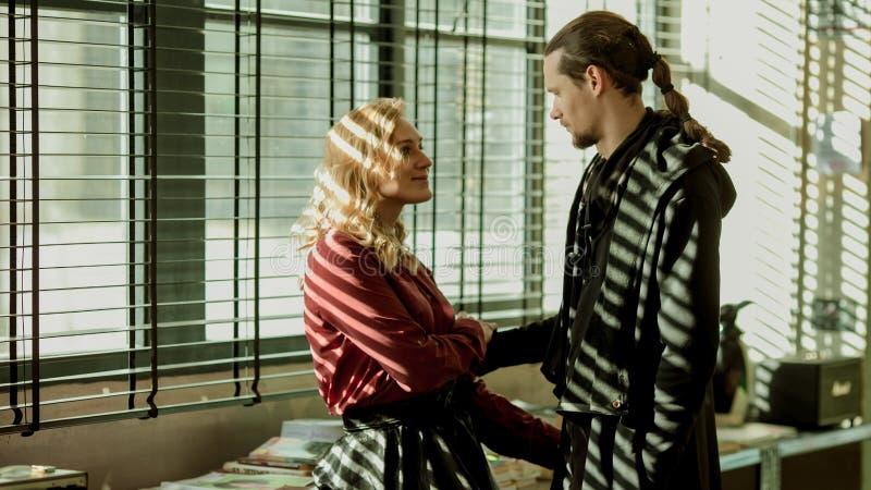 Dziewczyna i mężczyzna blisko okno, oczkujemy mężczyzna, śliczni związki, para w miłości, blond dziewczyna, uśmiechnięta kobieta  zdjęcia royalty free