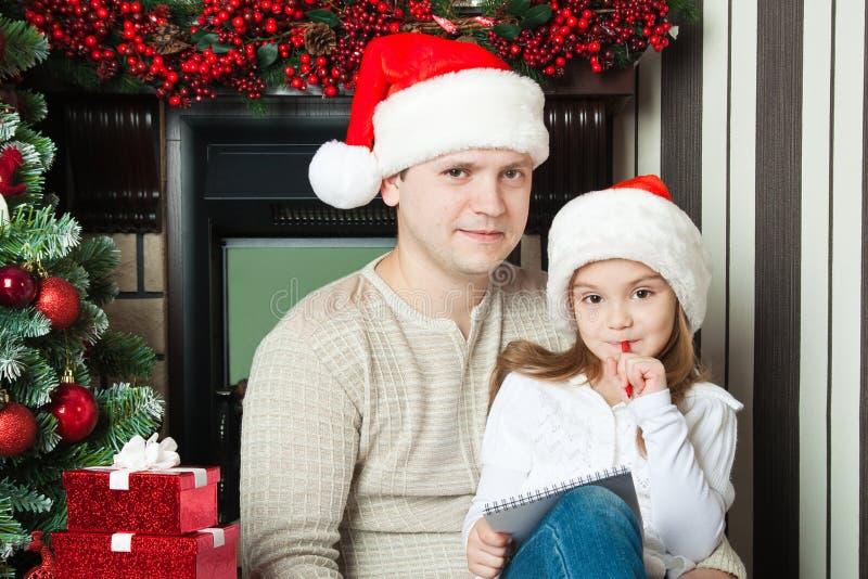 Dziewczyna i ojciec w kapeluszach piszemy liście Santa zdjęcie stock