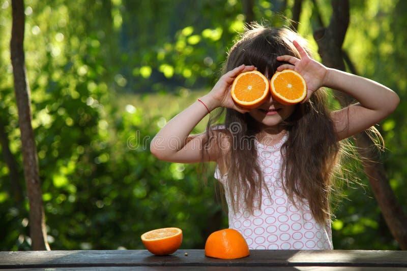 Dziewczyna i pomarańcze Dziewczyna bawić się z pomarańczami przy stołem w naturze dziecka owocowej dziewczyny szczęśliwe domowe m obraz royalty free