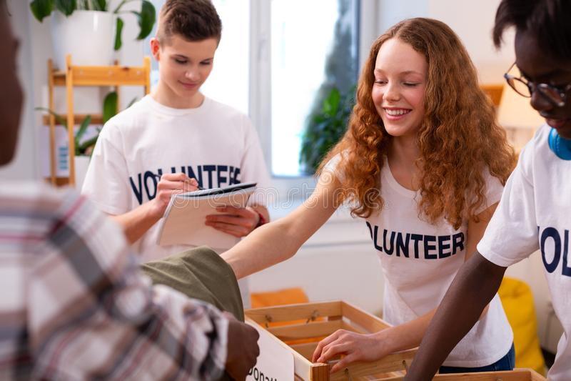 Dziewczyna i przyjaciele stawia niektóre odziewamy dla darowizny w pudełka zdjęcia royalty free