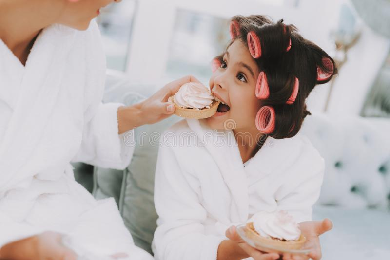 Dziewczyna Je babeczkę w zdroju salonie z Curlers fotografia stock