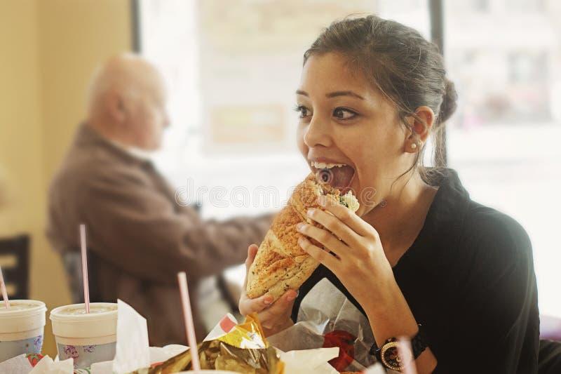 Dziewczyna je dużą kanapkę fotografia royalty free