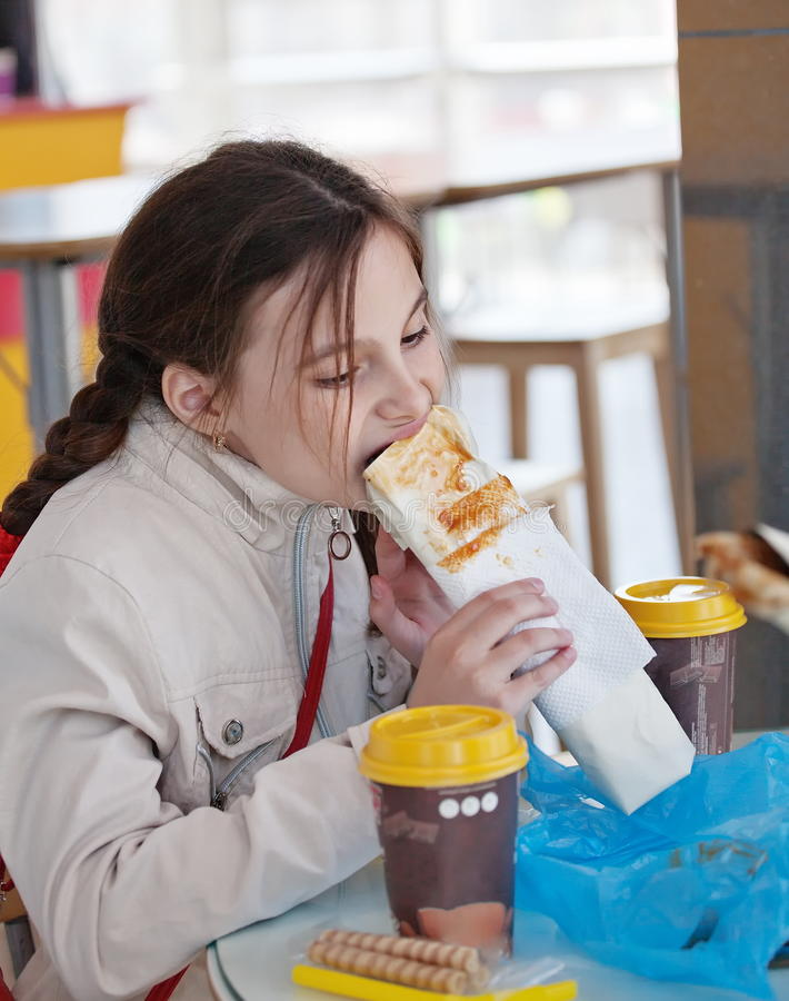 Dziewczyna je hot dog w kawiarni obraz stock