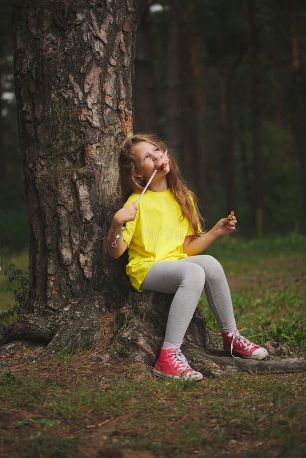 Dziewczyna je kiełbasę w lato lesie obrazy stock