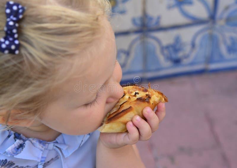 Dziewczyna je Pasteis de Belem jajeczny tarta, typowy Portugalski deser zdjęcia stock