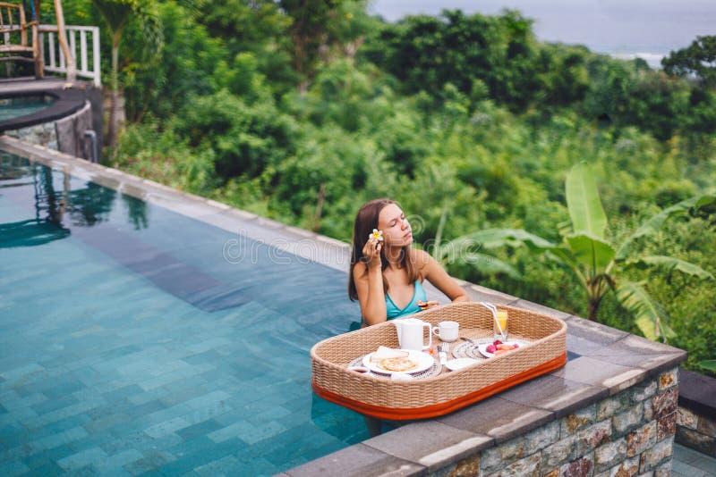 Dziewczyna je spławowego śniadanie w luksusowym nieskończoność basenie obrazy stock