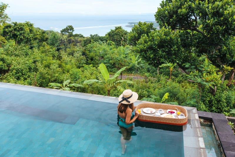 Dziewczyna je spławowego śniadanie w luksusowym nieskończoność basenie zdjęcie stock