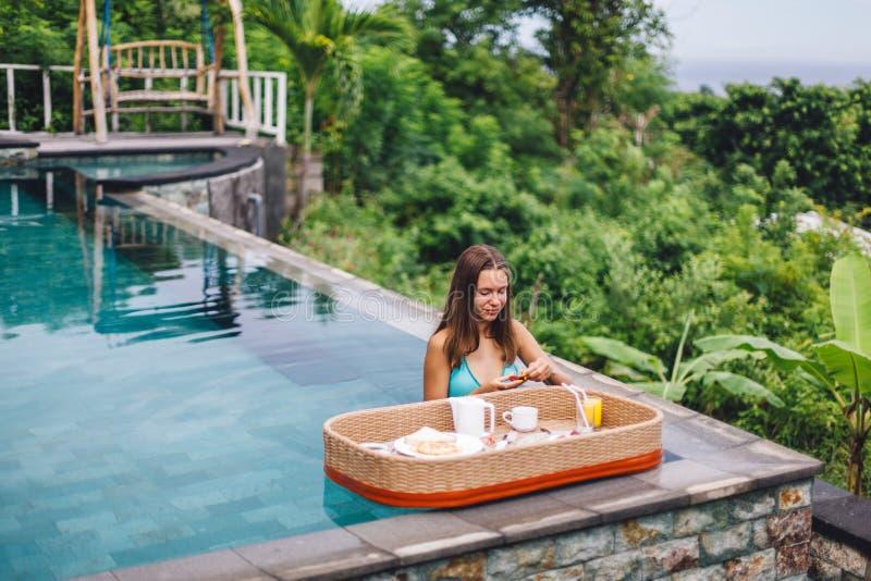 Dziewczyna je spławowego śniadanie w luksusowym nieskończoność basenie zdjęcia stock