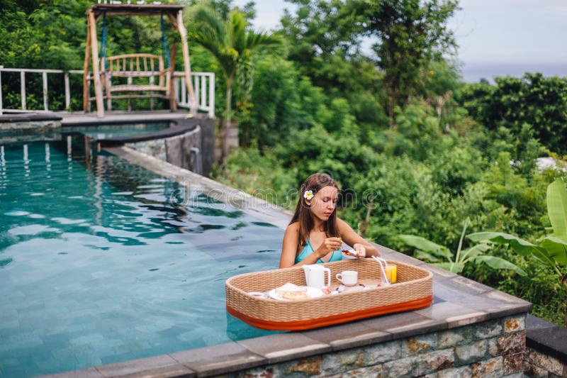 Dziewczyna je spławowego śniadanie w luksusowym nieskończoność basenie obraz royalty free