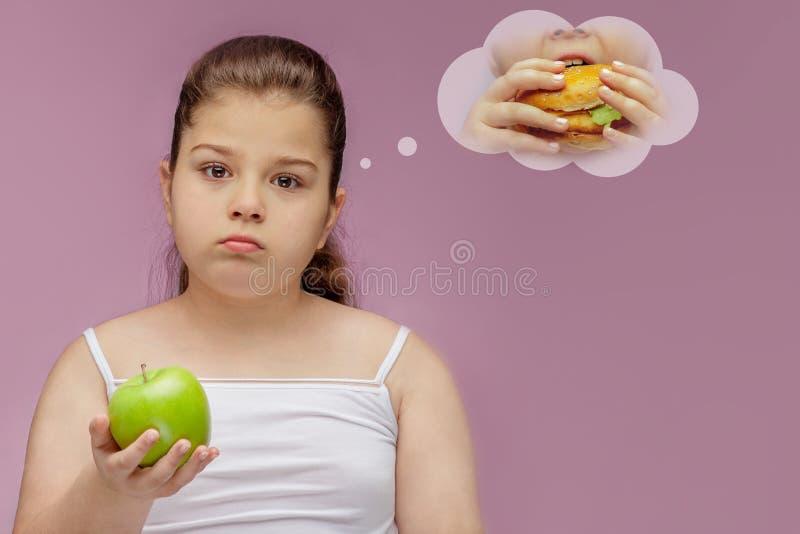 Dziewczyna je zielonego Apple ale marzy o hamburgerze, Harmonijny i zdrowy jedzenie dla dzieci Dziecko je zdrow? przek?sk? obrazy royalty free