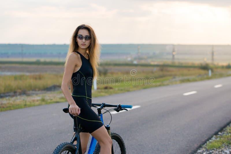 Dziewczyna jedzie rower górskiego na asfaltowej drodze, piękny portret cyklista obraz royalty free