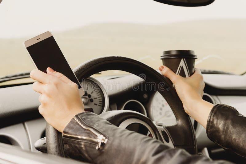 Dziewczyna jedzie samochodu pisać na maszynie tekst na telefonie out i przyglądający okno obrazy royalty free