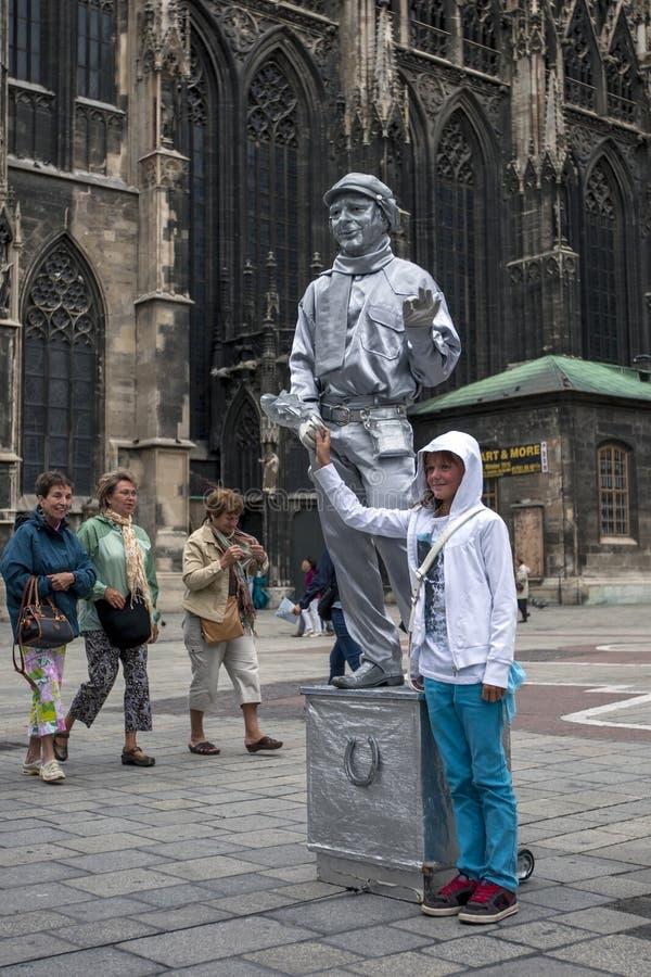 Dziewczyna jej fotografię brać z statua ulicznym wykonawcą malującym w srebrze w Wiedeń w Austria fotografia stock