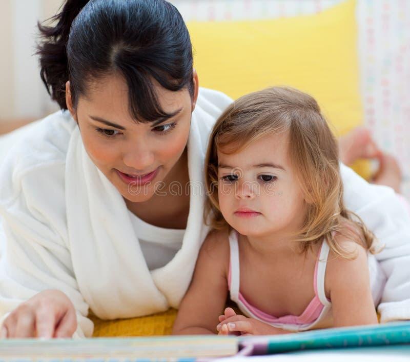 dziewczyna jej mały lying on the beach matki czytanie obraz royalty free