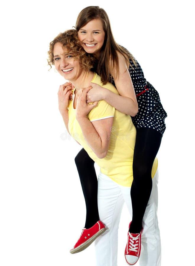dziewczyna jej matka piggybacks nastoletniego zdjęcia royalty free