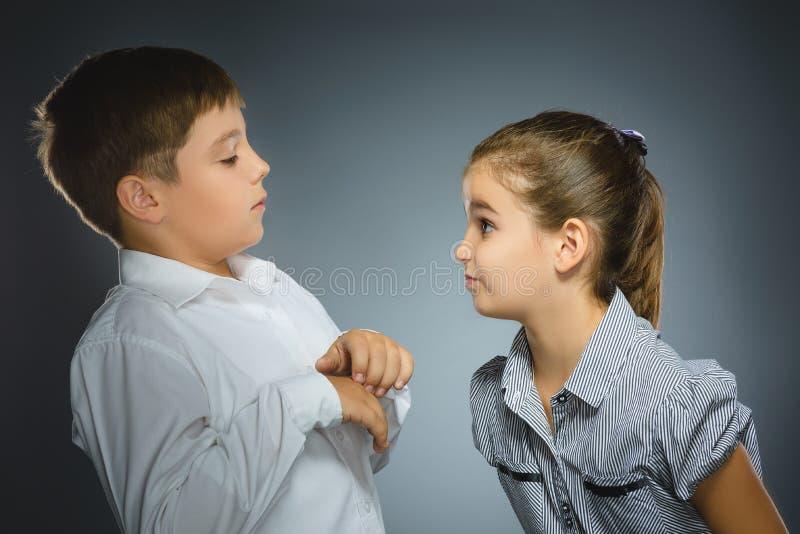 Dziewczyna jest gniewna przy przelękłą chłopiec na szarym tle czarny komunikacji koncepcji odbiorców telefon fotografia stock